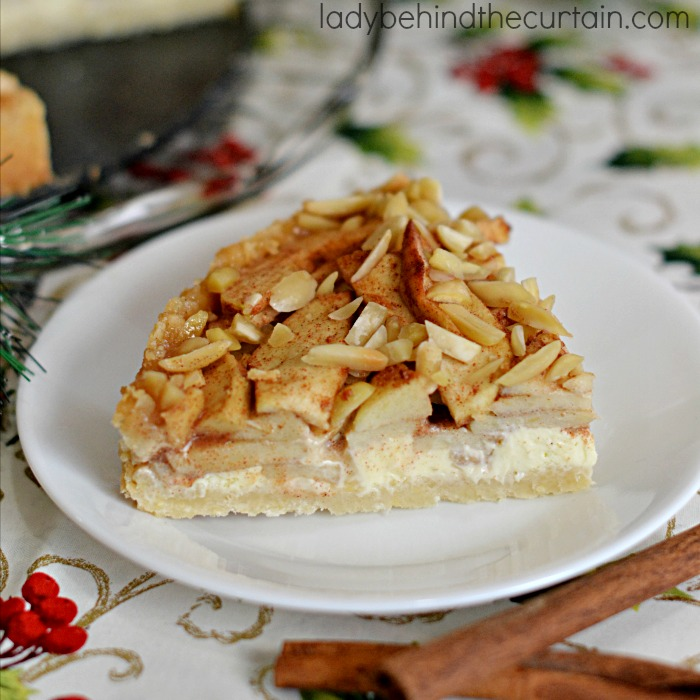 Apple Danish Cheesecake | This cheesecake starts with a delightful almond crust a thin layer of cheesecake all topped with tart apple rolled in a brown sugar cinnamon mixture and almonds.