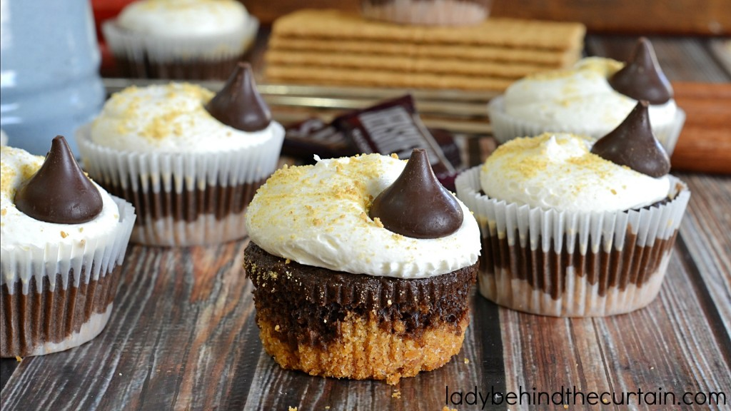 Easy S'more Cupcake Recipe | Bring back childhood memories of sitting around the campfire singing songs and roasting marshmallows with these fun easy to make cupcakes. They are my absolute favorite cupcakes. I love the graham cracker bottom and the marshmallow frosting is simply the best! You don't have to be a professional baker to make something out of this world delicious.