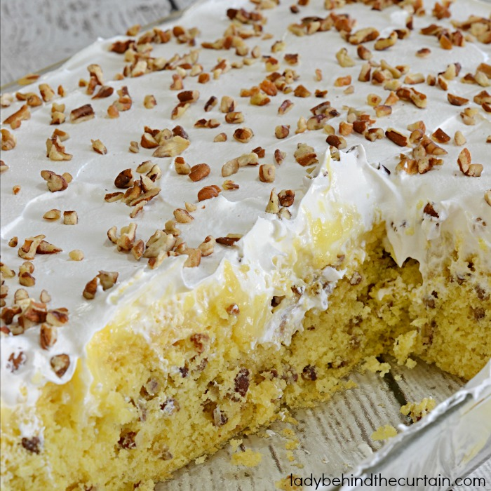 Hummingbird Poke Cake | The perfect potluck cake! Full of pecan, pineapple and banana flavor.